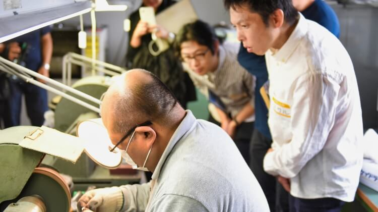 写真:松一の代表取締役・松澤さんが研磨機を扱う様子を眺める見学者の様子